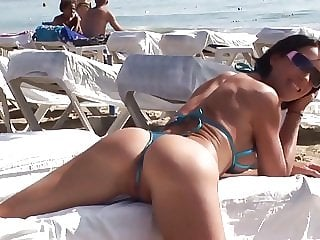 Hot brunette milf posing in sexy bikini on public beach
