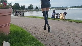 Sexy Blonde Lady in Tight skirt and High Boots by the lake